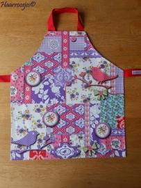 Kinderschortje, tafelzeil, paars patchwork met vogel met rode banden.