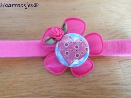 Babyhaarbandje, smal, fuchsia roze, met fuchsia roze bloem, hartje (op blauwe ruit) en een fuchsia roze roosje.