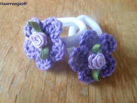 Zachte elastiekjes, groot, wit met paars gehaakt bloemetje met lila hartje en lila roosje.