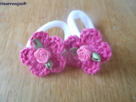 Zachte elastiekjes, groot, wit met fuchsia roze gehaakt bloemetje met roze hartje en roze roosje.
