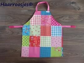 Kinderschortje, tafelzeil, gekleurd patchwork, roze banden.