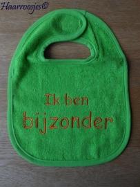 """Slabbetje, groen badstof met groen biaisband """"ik ben bijzonder""""."""