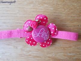 Babyhaarbandje, smal, fuchsia roze, met polakdot bloem,  `Lief` en een fuchsia roze roosje.