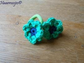 Zachte elastiekjes, groot,  groen met groen gehaakt bloemetje met donkerblauw hartje.