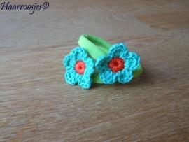 Zachte elastiekjes, groot,  groen met groen gehaakt bloemetje met oranje hartje.