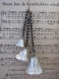 Antieke kerstdecoratie: zilveren klokjes aan glazen kralenkettinkjes