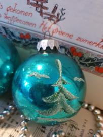 Oude kerstbal in kerstgroen met deco besuikerde dennenboompjes