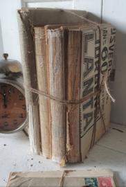 Bundel supersleetse oude boeken met jutetouw en vooroorlogse krant
