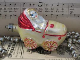 Oude kerstbal: Baby in kinderwagen. Besuikerd