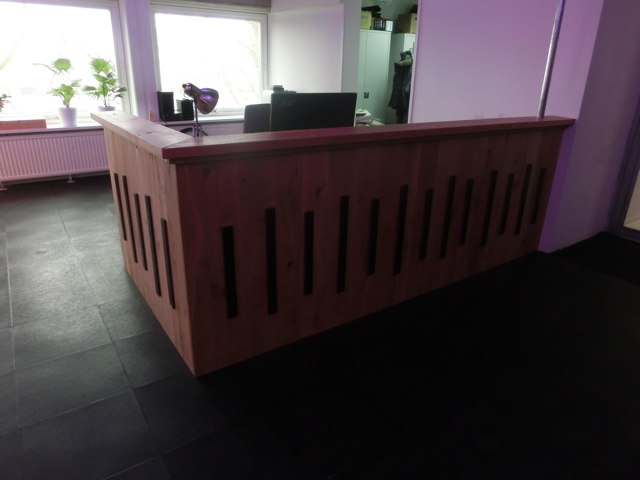 Op maat gemaakte houten balie bij Phidra