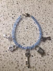 SALE - Armband van blauwe facetkraaltjes met 5 sleutelbedels