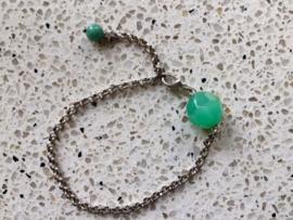 Zilverkleurige schakelarmband met groene facetkraal en bedeltje
