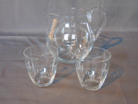 Clear glass water jug with drinking glasses