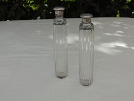 2 Crystal perfume bottles with silver plated caps.