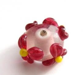 Lampwork kraal roze met een rood bloemetje.
