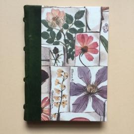 Handgemaakt notitieboek met donkergroen lederen rug en bloemen tekening.