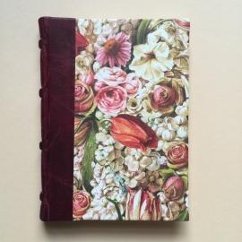Handgemaakt notitieboek met bordeaux rood lederen rug en rijk bloemen design.