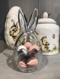 Glazen pot met konijnen oren gevuld met paaseitjes
