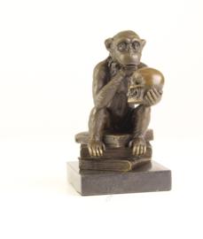 Bronzen chimpansee zittend op boeken