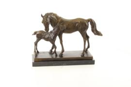 Een bronzen beeld van een merrie en veulen