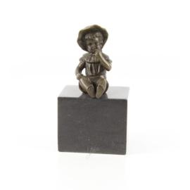 een bronzen meisje zittend op een marmeren sokkel