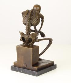 Bronzen beeld van de skelet denker op marmer basis.