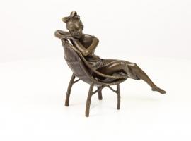 Bronzen beeld van meisje ontspannend in haar cirkel stoel.