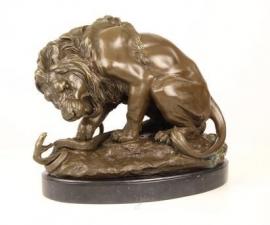 Bronzen beeld van een leeuw in gevecht met slang