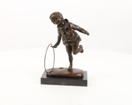 Een bronzen beeld jongen met hoepel