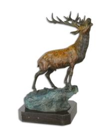 Een bronzen beeld van een HERT OP ROTS