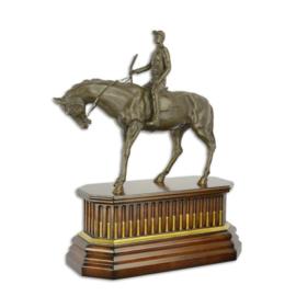 Een bronzen beeld van een jockey op paard op houten voet