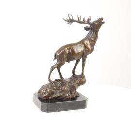 Bronzen beeld van een hert op een rots