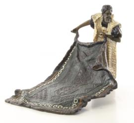 Een bronzen beeld van een Arabische tapijt verkoper