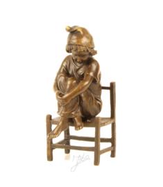 Schattig Bronzen beeldje meisje op de stoel.