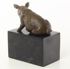 Een bronzen beeld van een zittende varken