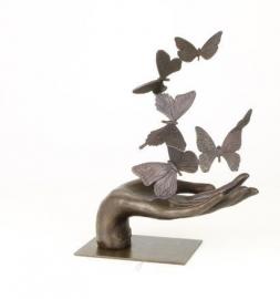 Bronzen beeld van een hand die vlinders loslaat
