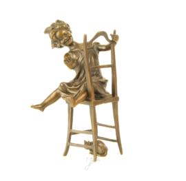 Beeldje van brons met een schattig meisje op stoel