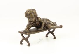 Schattig Bronzen beeldje van een kind met slak op de bank.