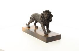 Een bronzen beeld van een leeuw gemonteerd op een houten plank