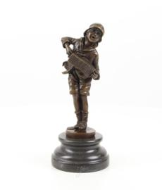 Bronzen jongen spelend op zijn Harmonica
