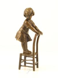 Lief beeldje van meisje staand op stoel