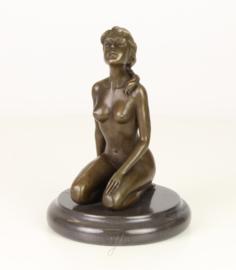 Bronzen beeld van een jonge naakte vrouw gehurkt op haar knieën.