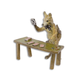 Een bronzen beeld van een vos met speelkaarten