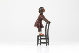 Bronzen beeldje van een schattig meisje op de kruk.