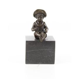 een bronzen jongen zittend op een marmeren sokkel