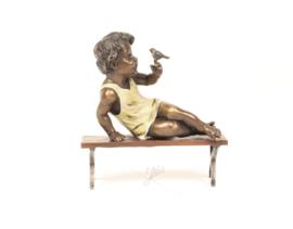 Brons beeldje van een schattig meisje met vogel in de hand.