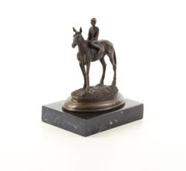 Een bronzen beeld van een paard en ruiter