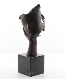 Een bronzen beeld van een gezicht dat op hand rust