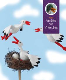 Drie vliegende ooievaars met nest