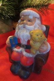 Stenen kerstman op stoel